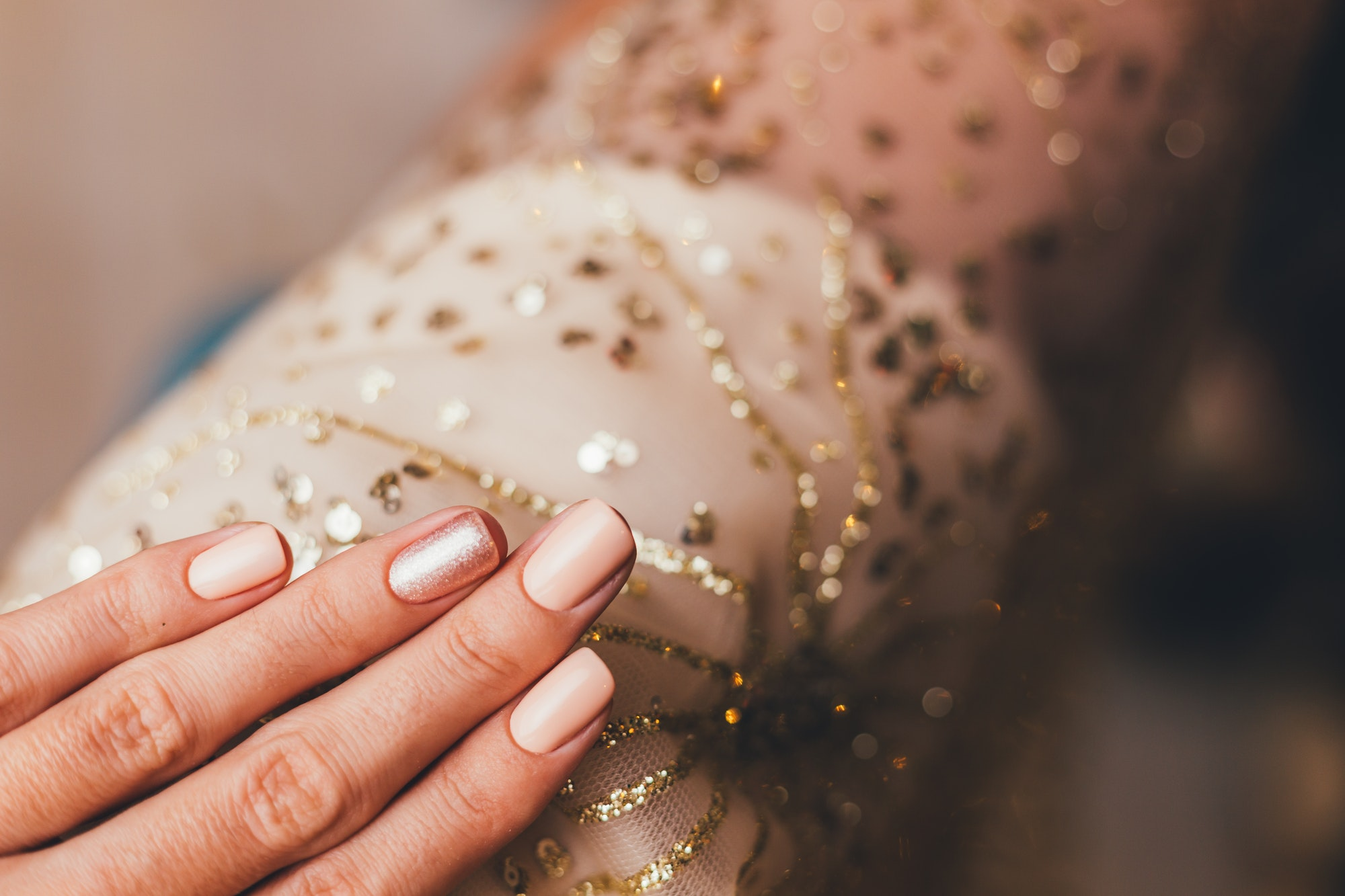 Female hands with Christmas new year nail design. Nude beige nail polish manicure